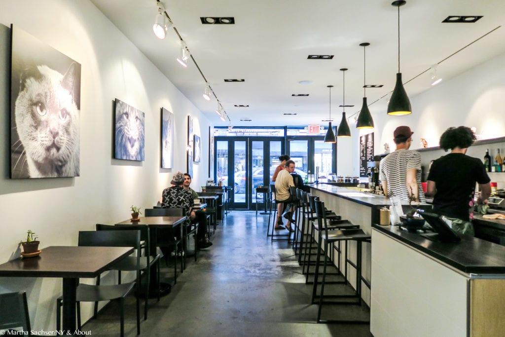 Área principal do Koneko Cafe, em Lower East Side, com quadros de gatos, mesas pretas e luzes pendentes